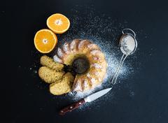 Moist orange bundt yoghurt cake with sugar powder, dark grunge background. To - stock photo