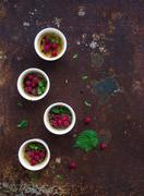 Creme brulees with raspberries and mint in white bowls over grunge metal back Stock Photos