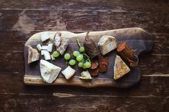 Wine appetizers set: meat and cheese selection, grapes and bread on a rustic  - stock photo
