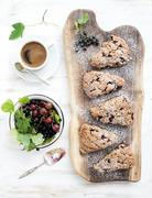 Fresh black-currant scones with coffee and bowl of berries over rustic walnut Stock Photos