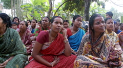 A small crowd of Indian women sitting on the ground, listening to an unseen - stock footage
