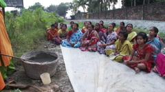 Women sitting on ground learning about making fertilizer Stock Footage