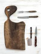 Kitchen-ware set. Old rustic chopping board made of walnut wood, knives, fork - stock photo