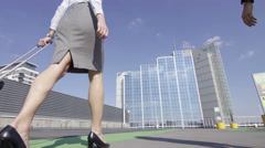 4K Businesswomen traveling together - walking with luggage towards airport Stock Footage