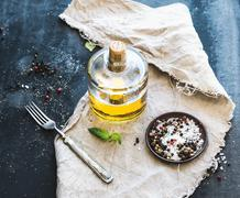 Bottle of olive oil with fresh basil and spices over dark grunge surface - stock photo
