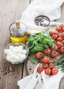 Basil, cherry-tomatoes, mozarella, olive oil, salt, spices on rustic chopping - stock photo