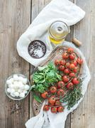 Basil, cherry-tomatoes, mozarella, olive oil, salt, spices on rustic chopping Stock Photos