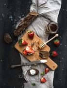 Breakfast set. Black baguette toasts with fresh strawberries, honey and masca Stock Photos