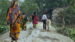 Villagers in India walking down dirt path Stock Footage