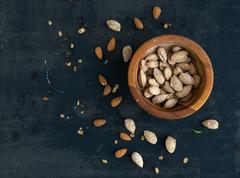 Wooden bowl of salty almond nuts in nutshell grunge dark backdrop, top view - stock photo