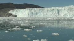 Handheld still of glacier front and sea filled with debris of ice Stock Footage
