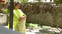 Lady in yellow sari leans against post Stock Footage