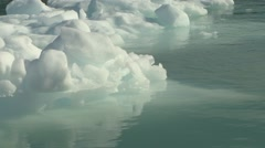 Handheld close up of ice floating in green arctic waters Stock Footage