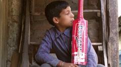 Boy looking, nodding holding red cricket bat Stock Footage