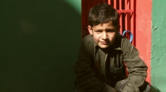 Boy sitting in front of red painted window and next to green walls Stock Footage