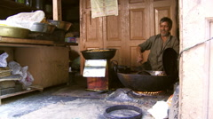 Man in kitchen frying food and pouring food into different container cooking Stock Footage