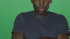 Young African American man crosses his arms and looks serious Stock Footage