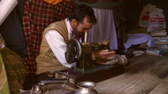 Man with pink measuring tape around his is sewing clothes on antique sewing Stock Footage