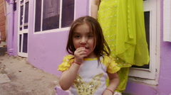 Little girl chewing on wrapper wearing yellow sleeved shirt lady in yellow Stock Footage