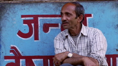 Man sitting outside shop on street in India Stock Footage