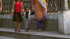 Women holding two girls hands walking down street in India Stock Footage