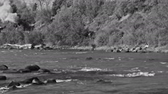 Black and white - Old steam train passes along river Stock Footage