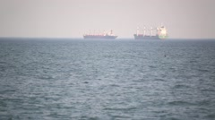two large barges are at anchor and waiting their turn to go through customs - stock footage