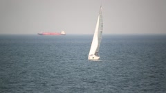 Sailing yacht day sails on the sea,followed behind the big ship Stock Footage