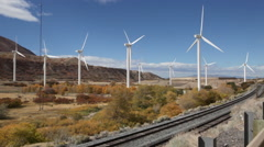 Nine wind turbines in a canyon seen from behind. Stock Footage