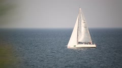 White sailboat floats through the frame in the sea Stock Footage