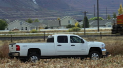 Chevy pickup in a cut corn field as a train passes behind. - stock footage