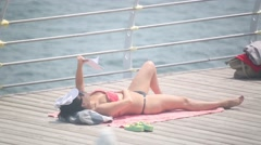 Girl lying on her back on a wooden pier against the sea and reading a book Stock Footage