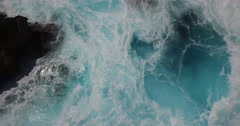 BEAUTIFUL CINEMATIC 4K AERIAL OF WAVES CRASHING AGAINST ROCK CLIFF Stock Footage