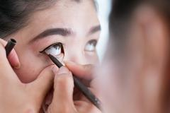 makeup beauty with brush eye liner on pretty woman - stock photo