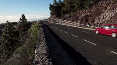 Small car drives on asphalt road TF-21 in Vilaflor village. Tenerife, Canaries Stock Footage