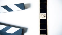 Movie clapper board and filmstrip Stock Footage