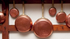 Row of vintage copper pans, different size, hung on wooden shelf in kitchen Stock Footage