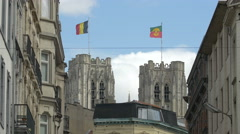 St Michael and St Gudula Cathedral's towers with flags in Brussels Stock Footage