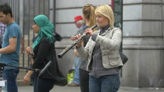 View of a woman playing an oboe on the street in Brussels Stock Footage