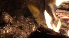 Potatoes wrapped in foil baking in the embers in the fireplace. - stock footage