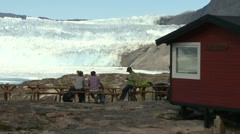 Guests being served at café in front of huge glacier Stock Footage