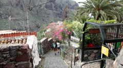 Tourists walk on the beautiful paved streets of Masca village, Tenerife Stock Footage