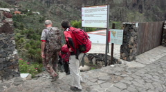 Group of hikers begins their walk from the start point in paved street of Masca Stock Footage