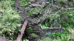 Hikers forces the river on bridge on the hiking route through the Masca gorge Stock Footage