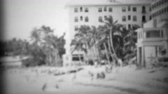 1953: Historic Moana Surfrider beach hotel with tourists frollicking about. Stock Footage
