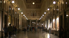 Tourists walking in Saint-Hubert Royal Galleries at night in Brussels Stock Footage