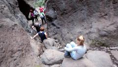 Mature people overcome the stony passageway when hiking in Masca Gorge, Tenerife Stock Footage