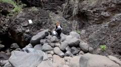 Mother and daughter overcome the stony passageway when hiking in Masca, Tenerife Stock Footage