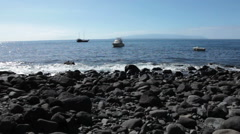 Stony beach at the end of Masca hiking trail. People wait ship to Los Gigantes Stock Footage