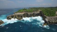 4K AERIAL POI SHOT OF MASSIVE ROCK CLIFFS AND OCEAN WAVES BELOW - stock footage